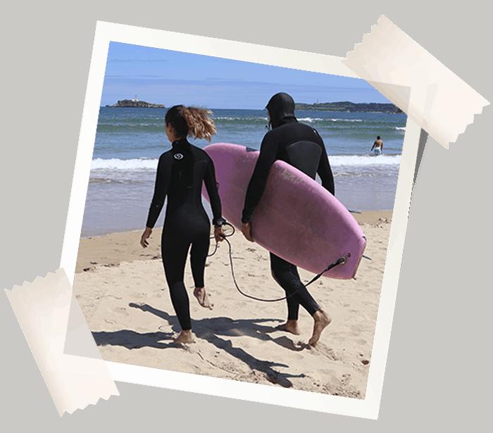 Eme y Ale hacia el agua con la tabla de surf
