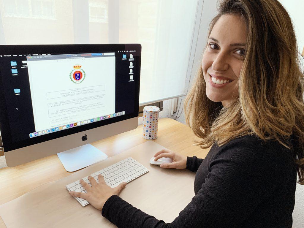 Eme cabanyes, mujer con discapacidad, posa delante del ordenador junto a su tesis doctoral